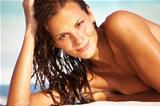Closeup of topless young woman smiling while relaxing