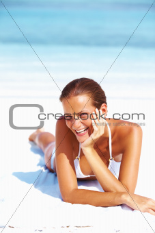 Portrait of young woman smiling while relaxing on beach