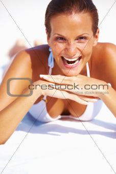 Portrait of cheerful young woman laughing while relaxing on beach