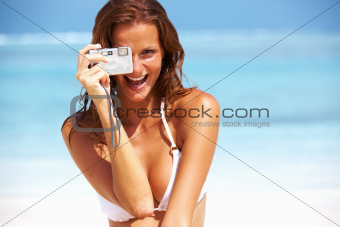 Portrait of gorgeous woman smiling while holding camera outdoors