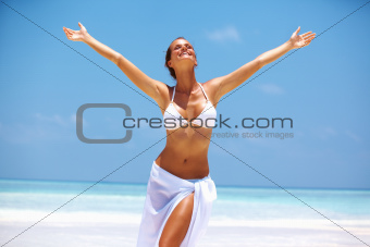 Portrait of carefree woman enjoying with arms outstretched at beach