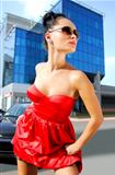 independent brunette in sunglasses on street
