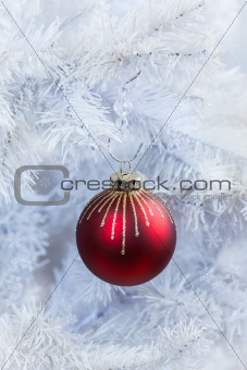 Red Christmas ball hanging on white tree