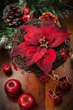 Christmas flower with decoration on wooden table
