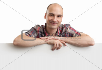Happy young man showing placard ready for your text