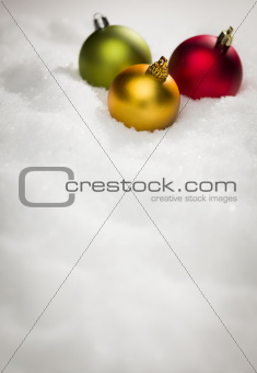 Beautiful Various Colored Christmas Ornaments on Snow Flakes Room For Your Own Text.