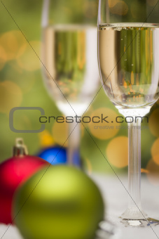 Beautiful Various Colored Christmas Ornaments and Champagne Glasses on Snow Flakes In Front of an Abstract Background.