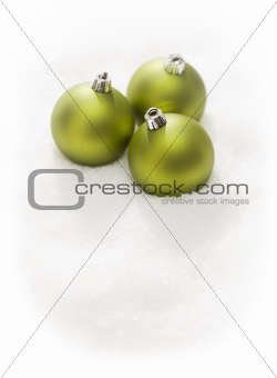 Three Green Christmas Ornaments on Snow Flakes Isolated on a White Background