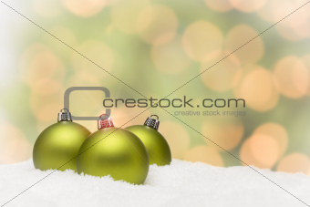 Beautiful Matt Green Christmas Ornaments on Snow Flakes Over an Abstract Background with Room For Your Own Text.
