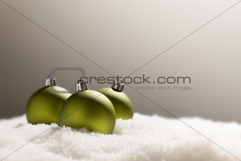 Green Christmas Ornaments on Snow Flakes Over a Grey Background