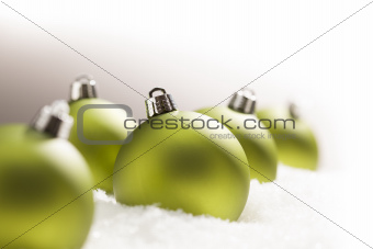 Green Christmas Ornaments on Snow Flakes Over a Grey Background, White at the Top and Right - Great for a Corner Image.