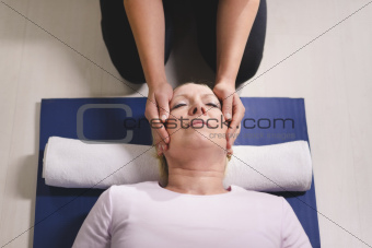 Young therapist doing reiki therapy to senior woman