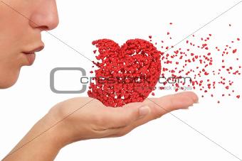 Woman blowing a heart