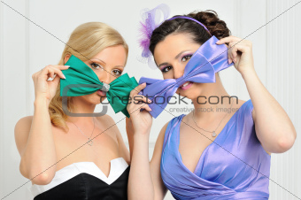 Two beautiful woman in evening gowns having fun.
