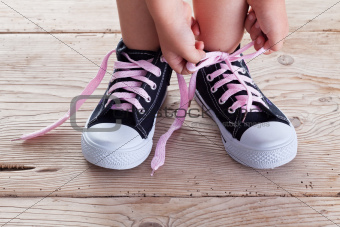 Child hands tie up shoe laces