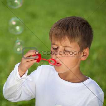 Boy having fun with bubbles on a green meadow