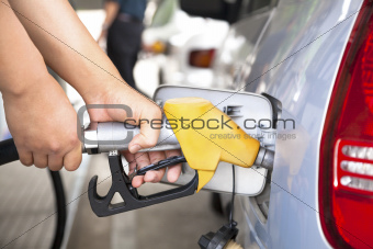 hand refilling the car with fuel on a filling station