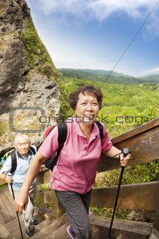 happy asian senior couple hiking in the mountain