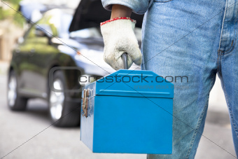 car mechanic holding toolbox and standing before vehicle