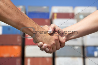 two business man handshaking before stack of containers