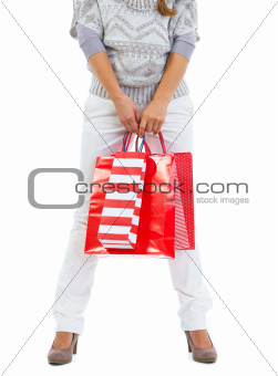Closeup on woman standing with red shopping bags