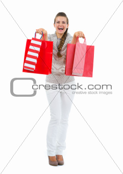 Happy woman in sweater with red shopping bags