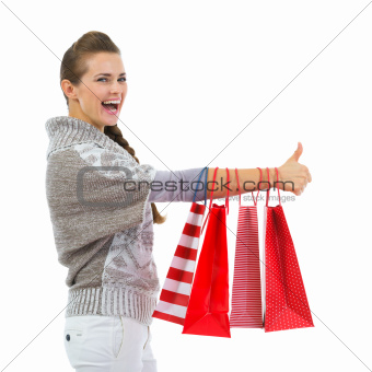 Happy woman in sweater showing thumbs up with shopping bags