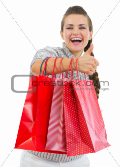 Smiling woman in sweater showing thumbs up with shopping bags