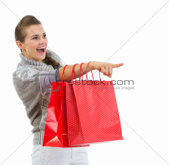Happy woman in sweater with shopping bags pointing on copy space