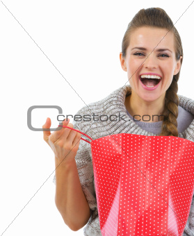 Smiling woman in sweater opening shopping bag