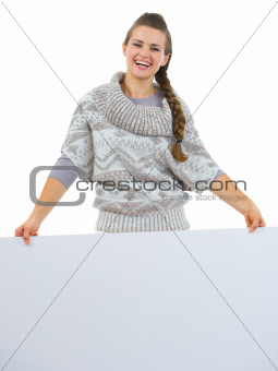 Smiling woman in sweater holding blank billboard