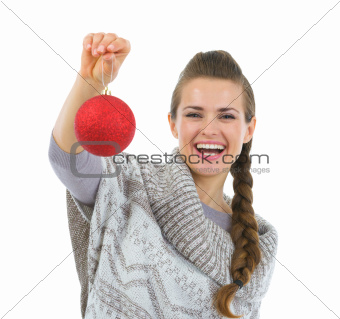 Smiling woman in sweater holding Christmas ball
