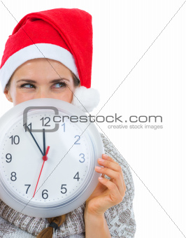 Woman in Santa hat holding clock in front of face and looking on copy space