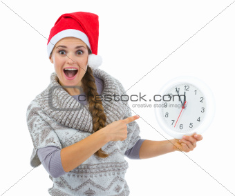 Surprised woman in Santa hat pointing on clock