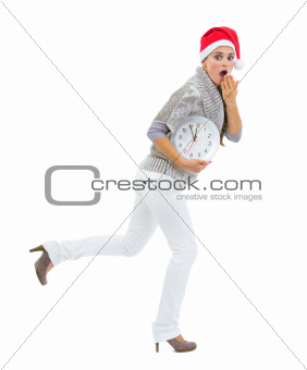 Shocked woman in Santa hat holding clock and running