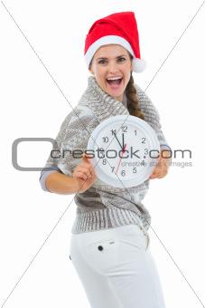 Happy woman in Santa hat showing clock
