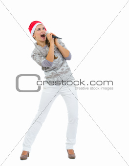 Happy woman in Santa hat singing in microphone and looking on copy space
