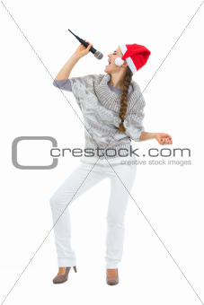 Happy woman in Santa hat singing in microphone