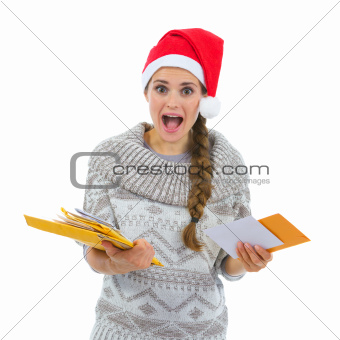 Shocked woman in Santa hat surprised by lots of Christmas letters