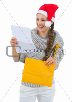 Happy woman in Santa hat reading Christmas letter
