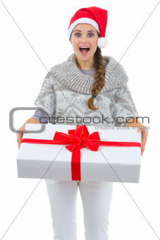 Surprised woman in Santa hat holding big Christmas present