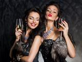 New Year&#39;s Eve of two beautiful young women with wine glasses