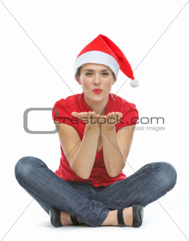 Happy young woman with Christmas hat sitting on floor and blowing kiss