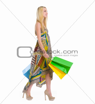 Happy girl in dress walking with shopping bags