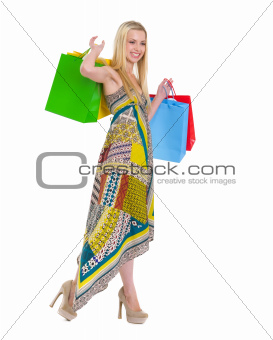 Smiling girl in dress with shopping bags