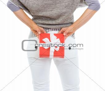 Closeup on woman hiding Christmas gift box behind back