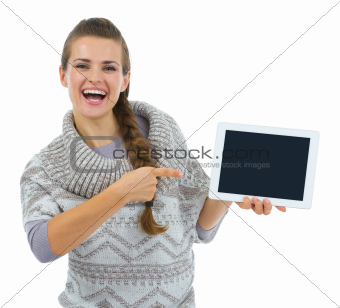 Smiling woman in sweater pointing on tablet PC blank screen