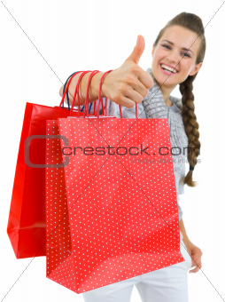 Closeup on showing thumbs up woman hand with shopping bags