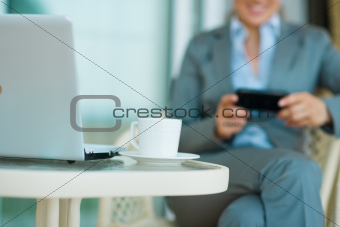 Closeup on table with laptop and business woman in background