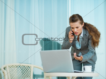 Concerned business woman speaking mobile and looking in laptop